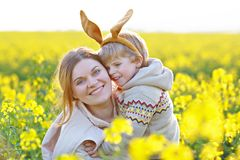 Petit enfant d'enfant en bas âge et sa mère dans des oreilles de lapin de Pâques ayant Image stock
