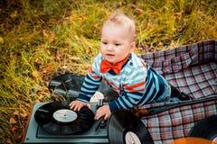 Petit enfant d'un an s'asseyant dans une vieille rétro valise en automne dehors photos libres de droits