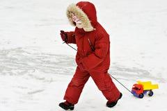 Petit enfant dans des vêtements de l'hiver avec la machine à écrire Image stock