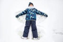 Petit enfant doux, garçon, se trouvant sur la neige de Pôle Nord, faisant la neige a Image stock