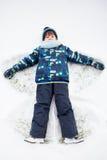 Petit enfant doux, garçon, se trouvant sur la neige de Pôle Nord, faisant la neige a Images libres de droits