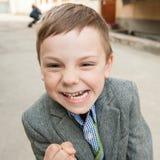 Petit enfant drôle avec la grimace sur son visage menaçant par son poing photo stock