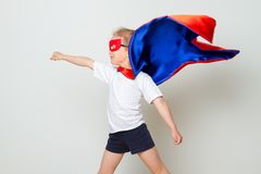Petit enfant drôle de superhéros de puissance dans un imperméable rouge Concept de superhéros Photographie stock