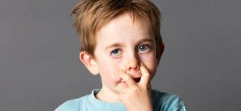 Petit enfant effronté avec des yeux bleus faisant une grimace laide Images libres de droits