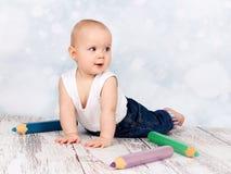 Petit enfant en bas âge adorable jouant avec de grands crayons Image libre de droits