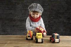Petit enfant en bas âge jouant avec les voitures en bois Image stock
