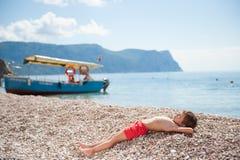 Petit enfant en bonne santé se trouvant sur la plage d'été sur la mer avec le fond en bois de bateau Photo stock
