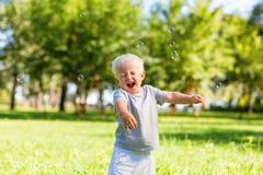 Petit enfant enthousiaste jouant dehors avec des bulles de savon photo stock