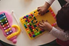 Petit enfant et clous colorés de champignon Photographie stock libre de droits