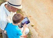 Petit-enfant et grand-père à l'aide d'un comprimé dehors Images libres de droits