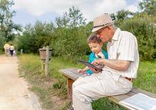 Petit-enfant et grand-père à l'aide d'un comprimé dehors Photographie stock