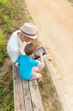 Petit-enfant et grand-père à l'aide d'un comprimé dehors Photos stock