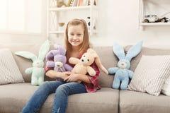 Petit enfant féminin heureux étreignant ses lapins de jouet sur le sofa à la maison images stock