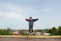 Petit enfant gai dans la veste sautant dans la perspective du port maritime Images libres de droits