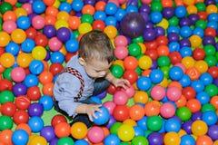 Petit enfant heureux jouant au terrain de jeu en plastique coloré de boules photographie stock