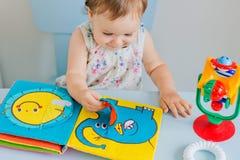 Petit enfant jouant avec le livre mou Image stock