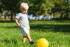 Petit enfant jouant avec une boule sur la nature photos stock