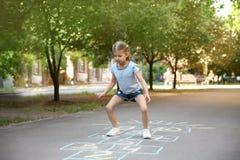 Petit enfant jouant le jeu de marelle dessiné avec la craie colorée images libres de droits