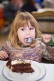 Petit enfant léchant la cuillère avec le gâteau de chocolat au restaurant Image libre de droits