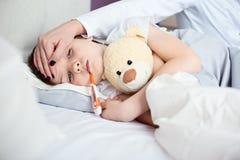 Petit enfant malade avec la température dans le lit image libre de droits