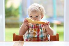 Petit enfant mangeant du pain avec du beurre image stock