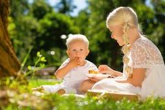 Petit enfant mangeant un gâteau ainsi qu'une soeur photographie stock