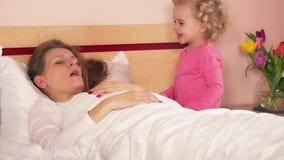 Petit enfant mignon éveillé sa mère de sommeil dans le matin clips vidéos