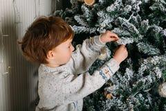 Petit enfant mignon décorant l'arbre de Noël avec les jouets en bois images libres de droits
