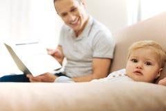 Petit enfant mignon détendant tandis qu'un père affectueux montrant des photos et le sourire Photos stock