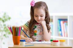 Petit enfant mignon d'élève du cours préparatoire dessinant à la maison Images stock