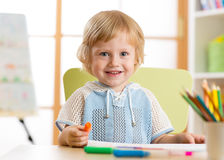 Petit enfant mignon d'élève du cours préparatoire dessinant à la maison Images libres de droits