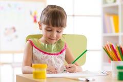 Petit enfant mignon d'élève du cours préparatoire dessinant à la maison Photos libres de droits