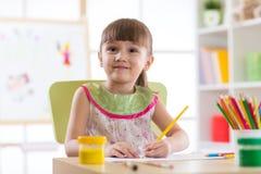 Petit enfant mignon d'élève du cours préparatoire dessinant à la maison Photos stock