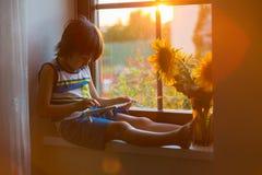 Petit enfant mignon d'enfant en bas âge, jouant avec l'abaque sur une fenêtre Image stock