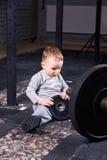 Petit enfant mignon dans le sportwear dans le gymnase convenable de croix avec un barbell Photographie stock