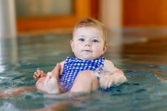 Petit enfant mignon de bébé apprenant à nager dans une piscine d'intérieur Photo libre de droits
