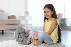 Petit enfant mignon jouant avec le lapin de jouet sur le plancher à l'intérieur photos stock