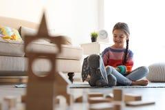 Petit enfant mignon jouant avec les blocs constitutifs en bois sur le plancher à l'intérieur photos stock