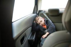 Petit enfant mignon portant les vêtements chauds dormant dedans à l'intérieur de la ceinture de sécurité de port de voiture photographie stock libre de droits