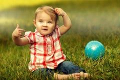 Petit enfant mignon s'asseyant sur l'herbe Photos libres de droits
