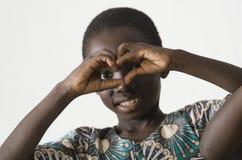 Petit enfant noir africain montrant le symbole de coeur avec ses mains, Images libres de droits
