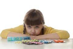 Petit enfant pleurant avec beaucoup de différentes pilules sur le blanc Danger d'intoxication de m?dicament photo stock