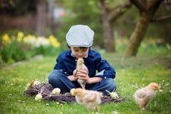 Petit enfant préscolaire mignon, garçon, jouant avec des oeufs de pâques et c Photo stock