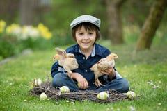 Petit enfant préscolaire mignon, garçon, jouant avec des oeufs de pâques et c Images libres de droits