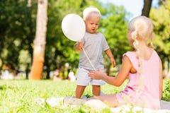 Petit enfant présent un ballon à une soeur photographie stock