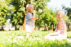 Petit enfant présent une fleur à une soeur image stock