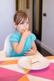 Petit enfant s'asseyant dans la chaise d'arbitre mangeant le morceau de gâteau Images stock