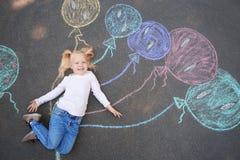 Petit enfant se trouvant près du dessin de craie des ballons sur l'asphalte photographie stock