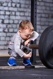 Petit enfant sportif avec le barbbell contre le mur de briques au gymnase convenable de croix Image stock