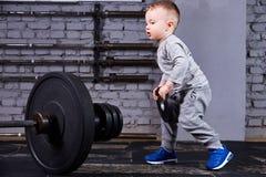 Petit enfant sportif avec le barbbell contre le mur de briques au gymnase convenable de croix Photo libre de droits